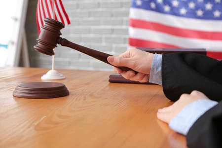 Female judge with gavel at table in courtroom, closeup