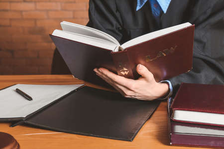 Female judge reading book at table in courtroom, closeup