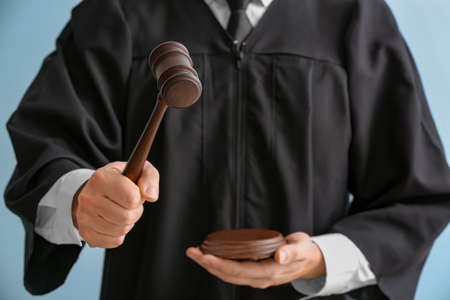 Male judge with gavel on light background, closeup