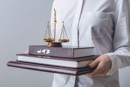 Female judge with books and scales of justice on light background, closeup