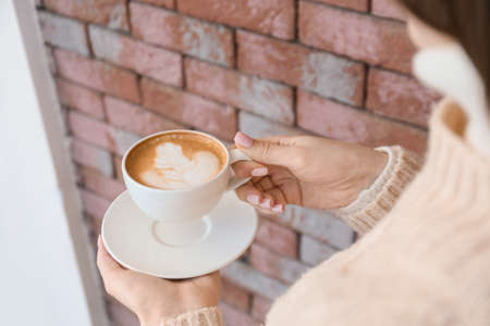 Woman with cup of tasty cappuccino outdoors, closeup Stockfoto