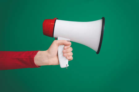 Hand of young woman with megaphone on color background
