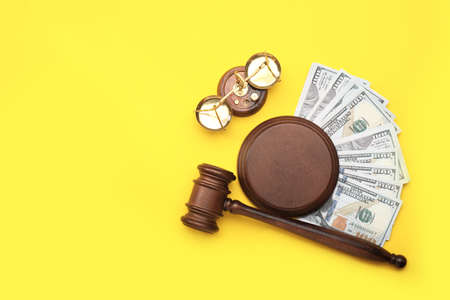 Judge's gavel, scales of justice and money on color background