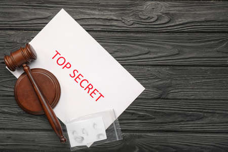 Judge's gavel, paper with text TOP SECRET and clue on wooden background