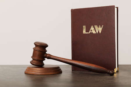 Judge's gavel and book on table against light background