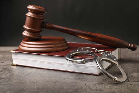 Judge's gavel, book and handcuffs on table against dark background
