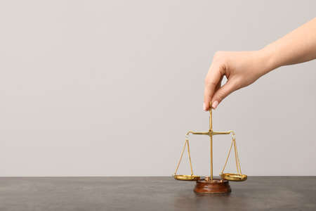 Female hand putting scales of justice on table