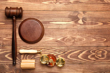 Judge's gavel, stamps and scales of justice on wooden background