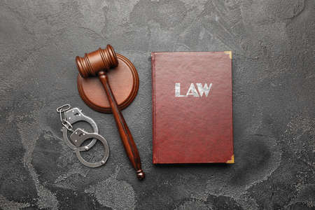 Judge's gavel, book and handcuffs on gray background