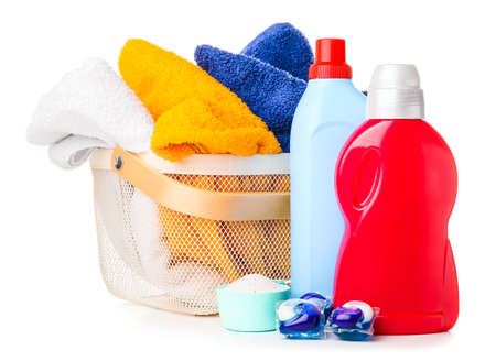 Basket with towels and laundry detergents on white background