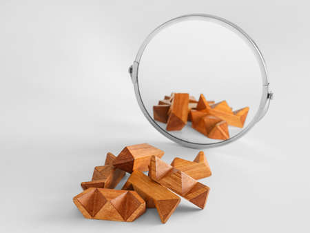 Wooden puzzle near mirror on light background