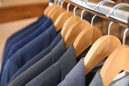 Hanger with different stylish male suits, closeup Foto de archivo