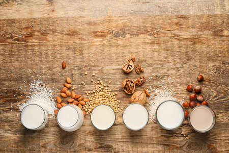 Glasses of different milk on wooden background