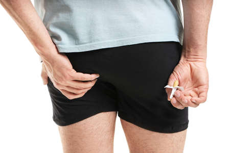 Young man with hemorrhoidal suppository on white background, closeup