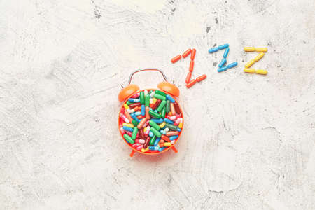 Alarm clock and sleeping pills on light background