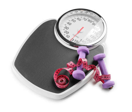 Weight scales with measuring tape and dumbbells on white background. Slimming concept