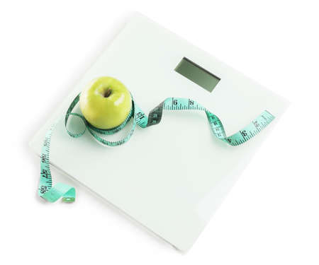 Weight scales with measuring tape and apple on white background. Slimming concept
