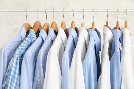 Rack with clothes on light background Foto de archivo