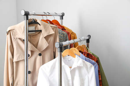 Rack with clothes on light background