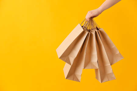 Female hand with paper shopping bags on color background
