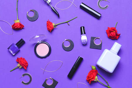 Makeup cosmetics with accessories on color background
