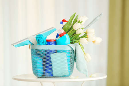 Set of cleaning supplies and spring flowers on table in room
