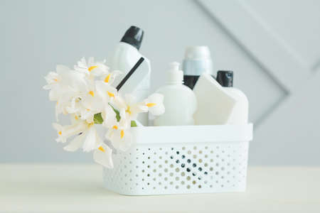 Set of cleaning supplies and spring flowers on gray background