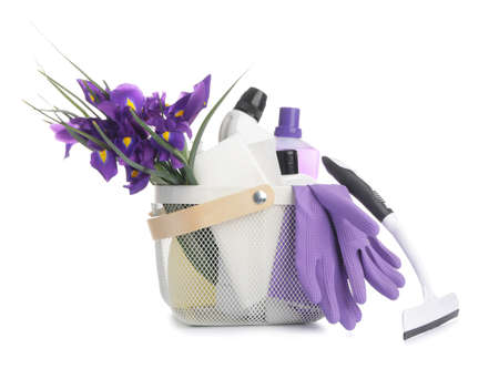 Set of cleaning supplies and spring flowers on white background