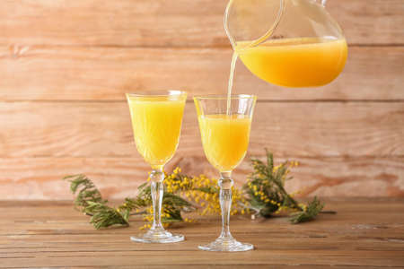 Preparing of tasty mimosa cocktail on wooden background