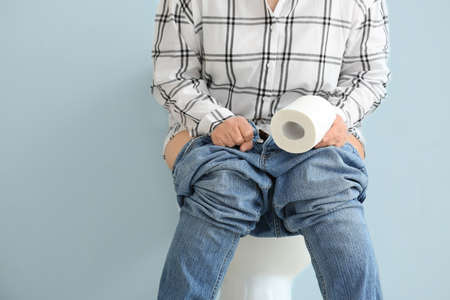 Elderly woman with paper sitting on toilet bowl against color background. Concept of hemorrhoids