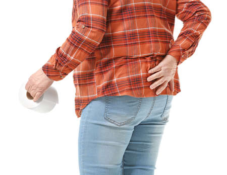 Elderly woman with toilet paper suffering from hemorrhoids on white background