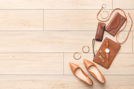 Set of female accessories on light wooden background