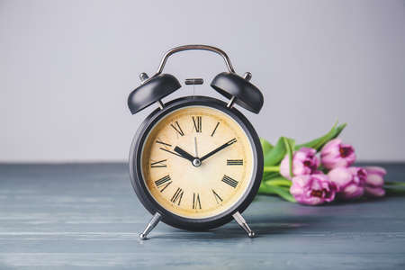 Alarm clock and flowers on table. Spring time Imagens