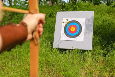 Woman practicing archery in forest, closeup