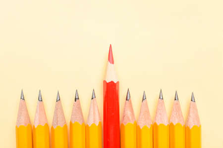 Red pencil among ordinary ones on color background. Concept of uniqueness Stock Photo