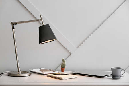 Modern lamp and stationery on table in room Reklamní fotografie