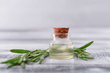 Bottle of rosemary essential oil on table