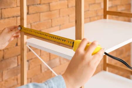 Young woman measuring shelf unit indoors, closeup Standard-Bild
