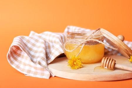 Jar of dandelion honey on color background Stockfoto