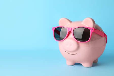 Piggy bank with sunglasses on color background Reklamní fotografie