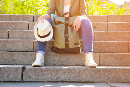 Female traveler with backpack sitting on steps in park