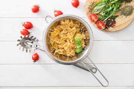 Dry pasta with spices and tomatoes on table