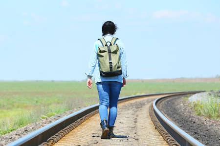 Female traveler with backpack walking along railway tracks
