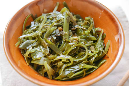 Bowl with tasty seaweed on table, closeup