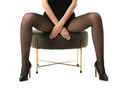 Beautiful young woman in tights sitting on pouf against white background Archivio Fotografico