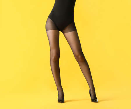 Legs of beautiful young woman in tights on color background