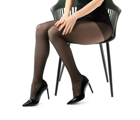 Beautiful young woman in tights sitting on chair against white background
