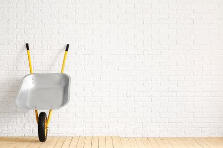 Empty wheelbarrow near white brick wall