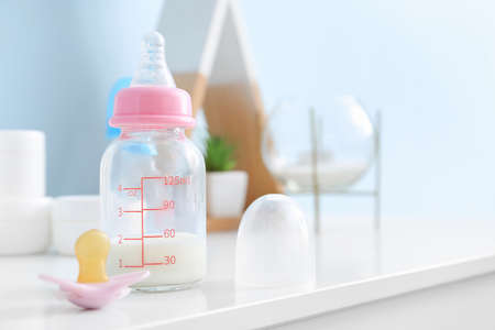 Bottle of milk for baby with pacifier on table