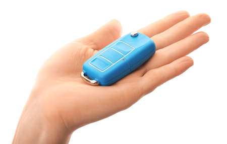 Female hand with car key on white background